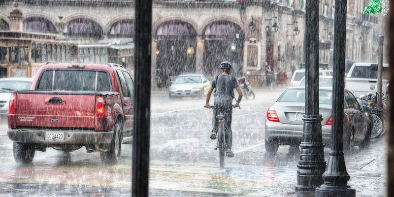 Photo of a cyclist riding in very heavy rain