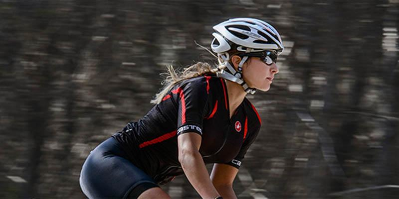 Photo of a lady wearing a white bike helmet at speed